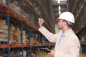 worker counting stocks in warehouse